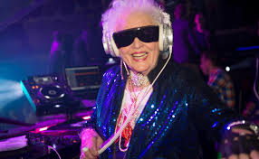 white woman with white hair and big black sunglassed in night club in front of turntable.