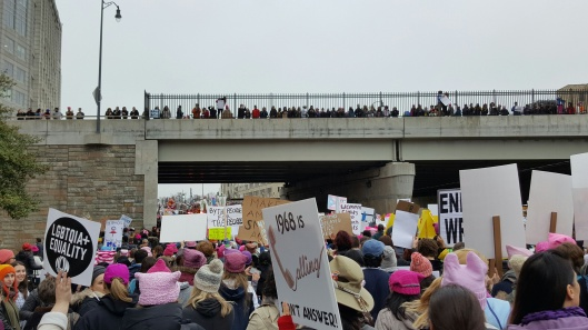 marchers in street with people lining the overpass as it travels through L'Enfant Plaza in Washnington D.C. Sign in forground says,
