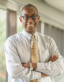 Photo of Charles Syms, African American man,standing wiih arms crossed over chest, smiling, wearing white shirt, yellow tie, and eyeglasses.