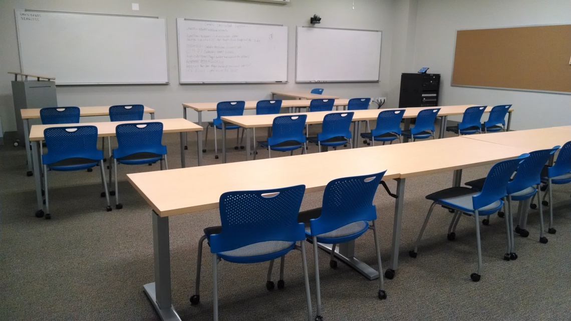 Image of an empty classroom. Classroom has three rows of tables with blue chairs. In front of the classroom is 3 large white boards.