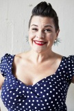 Smiling white woman, about 45 years old, in blue with white polka-dot dress wiht deep sweetheart neckline; she has dark brown hair in a punkish, almost-Mohawk style.