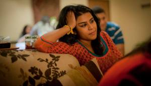 Shaanta Murshid props her head on on one hand as she relaxes on a couch.