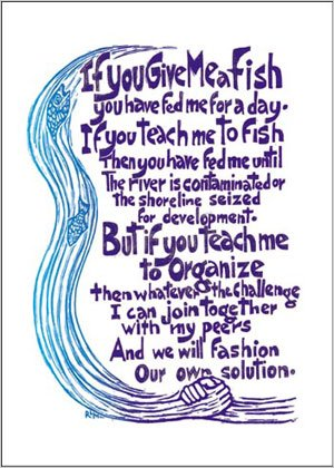 poster with two hands grasping; and the text: If you give me a fish you have fed me for a day. If you teach me to fish then you have fed me until the river is contaminated or the shoreline seized for development. But if you teach me to organize then whatever the challenge I can join together with my peers and we will fashion our own solution.